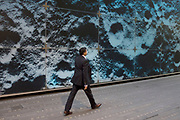 Workers in the City of London walk past a large scale lunar landscape. It is a strange vista as people wearing suits not space suits interract with the surface of the Moon. UK.