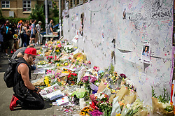© Licensed to London News Pictures. 17/06/2017. London, UK. A man looks at floral tributes left for the victims of Grenfell tower block in west London following a devastating fire earlier this week. The blaze engulfed the 27-storey building killing 12 - with 34 people still in hospital, 18 of whom are in critical condition. The fire brigade say that they don't expect to find anyone else alive. Photo credit: Ben Cawthra/LNP