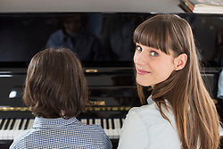 Mother and daughter playing piano, close up