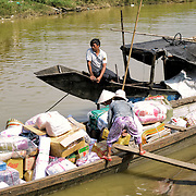 A woman loads up her sampan with supplies from the Dong Ba market on the Perfume River in Hue, Vietnam.