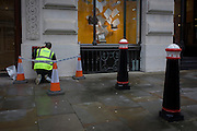 Worker with contractor company Cousins paints metalwork within coned and taped-off site area in the financial City of London.