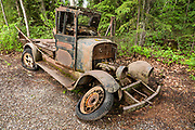 An old jalopy decays outdoors. Big Delta State Historical Park: Rika's Roadhouse served travelers on the historic Valdez-to-Fairbanks Trail from 1913 to 1947, at a historically important crossing of the Tanana River. Find it off mile 274.5 of the Richardson Highway in Big Delta, in the Southeast Fairbanks Area, Alaska, USA. Jovo 'John' Hajdukovich, an immigrant from Montenegro, had the north-south section of this log structure built in 1913. Starting in 1917, Swedish immigrant Rika Wallen operated this regional hub serving gold stampeders, local hunters, traders, and freighters; and she bought the roadhouse in 1923. With the construction of the ALCAN (now Alaska) Highway and the replacement of the ferry with a bridge downstream, traffic moved away and patronage declined.