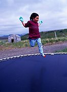 Yupik child Camry playing on trampoline, village of Twin Hills, Alaska.