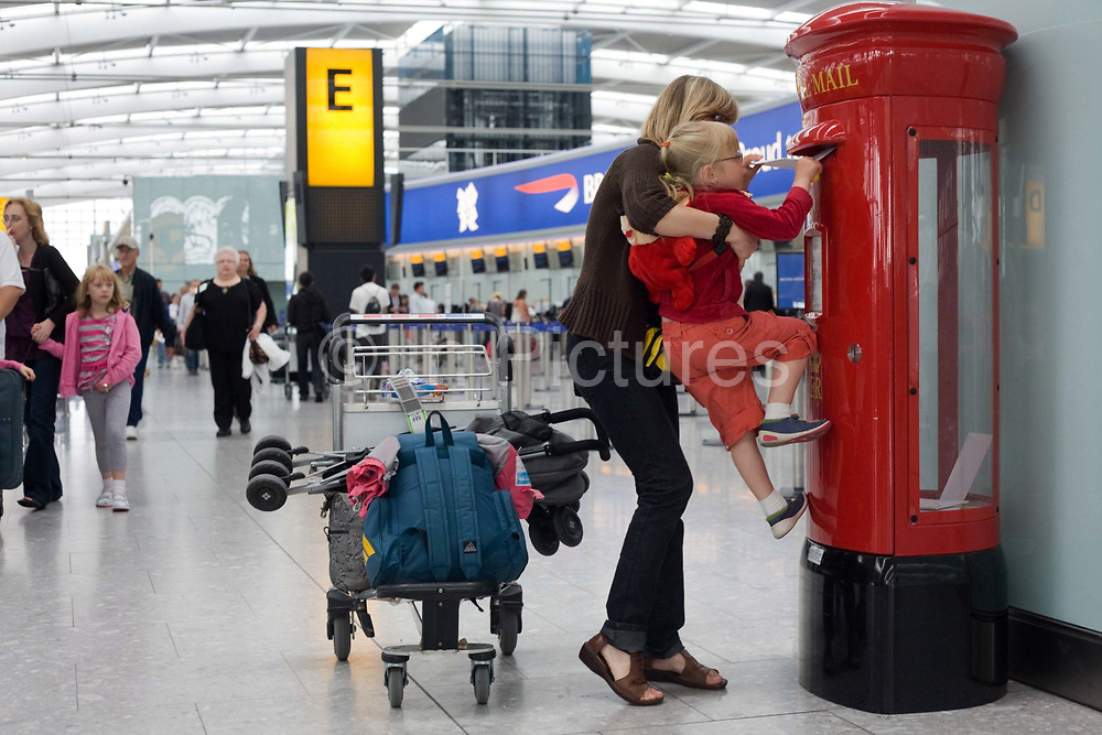 """A young mother holds up her daughter to insert a letter into a post box at Heathrow Airport's Terminal 5. The girl half-climbs up the red pillar box and tries to get the postage item into the narrow slot which is an even tighter fit because of security considerations - avoiding larger and potentially dangerous packages from entering the airport's postal system. In the background we see the bustle of a departures concourse where British Airways passengers walk past after having checked-in at BA's hub terminal. At a cost of £4.3 billion, Terminal 5 has the capacity to serve around 30 million passengers a year. From writer Alain de Botton's book project """"A Week at the Airport: A Heathrow Diary"""" (2009)."""