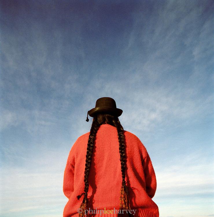 Profile portrait of woman in traditional dress on Salar de Uyuni salt flats, Potosi, Bolivia. The Salar de Uyuni are the worlds largest salt flats.
