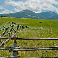 Fair weather cumulus clouds drift over pastures in Montana's Gallatin Valley, near Bozeman. Mount Ellis and the southern Gallatin Range rise in the background.