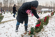Goshen, New York - A woman places an American flag on a wreath during a Wreaths Across America ceremony at Orange County Veterans Memorial Cemetery on Dec. 16, 2017. About 3,000 wreaths were placed at graves, and small American flags were added to the wreaths at veterans' graves.