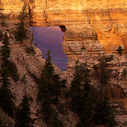 Angel's Window, a gaping hole in the sandstone wall, frames the Colorado River five thoudand feet below.