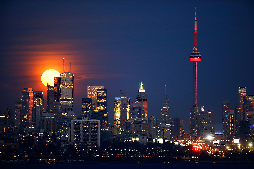 The moon rises behind the Canadian landmark, the CN Tower, and the skyline in Toronto, November 25, 2015.    REUTERS/Mark Blinch