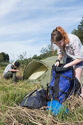Young woman searching in bag with her friend setting up tent in a forest, Bavaria, Germany
