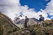 Day 4 of 10: In Tuctubamba Valley, trekkers ascending Tupatupa Pass pause below Nevado Taulliraju (19,100 ft or 5830 m). Trek 10 days around Alpamayo in Huascaran National Park (UNESCO World Heritage Site), Cordillera Blanca, Andes Mountains, Peru, South America.
