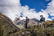 Day 4 of 10: In Tuctubamba Valley, trekkers ascending Tupatupa Pass pause below Nevado Taulliraju (19,100 ft or 5830 m). Trek 10 days around Alpamayo in Huascaran National Park (UNESCO World Heritage Site), Cordillera Blanca, Andes Mountains, Peru, South America.