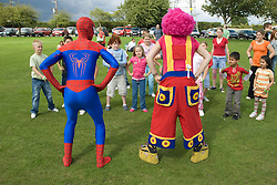 Group of children taking part in a Superhero workout with Spiderman and clown at a Parklife summer activities event,