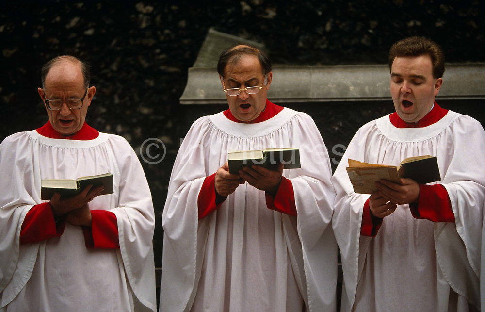 Three choristers sing hymns outside the Norman-built St Bartholomew the Great church in Smithfield, City of London. Open-mouthed they recite the songs with great enthusiasm, all looking down and concentrating on the Holy words from their songbooks. Dressed in white and red choir cassock robes they are all identical in their facial expression, their stance and posture. The Priory Church of St Bartholomew-the-Great is an Anglican church located at West Smithfield in the City of London, founded as an Augustinian priory in 1123.