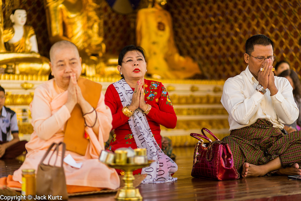 07 JUNE 2014 - YANGON, YANGON REGION, MYANMAR:  People pray at Shwedagon Pagoda in Yangon. Shwedagon Pagoda is officially called Shwedagon Zedi Daw and is also known as the Great Dagon Pagoda and the Golden Pagoda. It's a 99 metres (325ft) gilded pagoda and stupa located in Yangon. It is the most sacred Buddhist pagoda in Myanmar with relics of the past four Buddhas enshrined within: the staff of Kakusandha, the water filter of Koṇāgamana, a piece of the robe of Kassapa and eight strands of hair from Gautama, the historical Buddha.   PHOTO BY JACK KURTZ
