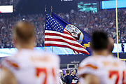 Kansas City Chiefs players stand as an American flag flies during the playing of the National Anthem before the 2017 NFL week 1 regular season football game against the New England Patriots, Thursday, Sept. 7, 2017 in Foxborough, Mass. The Chiefs won the game 42-27. (©Paul Anthony Spinelli)