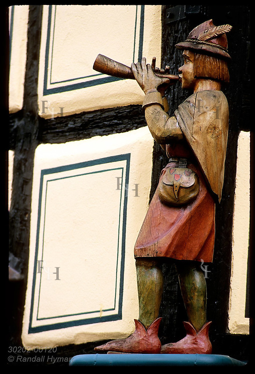 Wooden carving of a man playing a horn sits on ledge above restaurant in Ribeauville. France