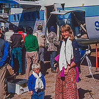 Draped with ceremonial Tibetan Buddhist kata prayer scarfs  Meredith Wiltsie and her 3-year old son Ben Wiltsie wait to board a flight at Lukla airstrip in the Khumbu region of Nepal, a dangerous and often overbooked journey.  .