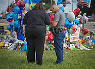"""Pj Freeman, A Louisiana <br /> State police officer, with a Timothy Williams, a Baton Rouge resdient,  at a makeshift memorial at the site  where six oifficers were shot on Airline Highway in Baton Rouge. The memorial in front of the  B-Quik gas station continues to grow. <br /> """"It just give you chills that this is the spot it happened,""""Freeman said."""