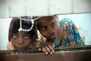 Jyoti, 10, (left) and her older sister Arti, 15, are curiously looking through a thin glass wall, while waiting for their turn to have a tooth inspection by a dentist in Bhopal, central India, near the abandoned Union Carbide (now DOW Chemical) industrial complex, site of the infamous '1984 Gas Disaster'.