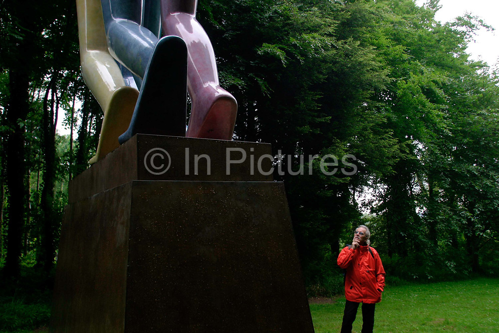 """A visitor admires a sculpture called """"Legs Walking"""" by Kenneth Armitage in the Goodwood Sculpture Park, Sussex, UK"""