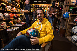 Fabrizio Caoduro of 70's Helmets in Italy in his shop-like Helmet display in Hall 10 with its all custom focus at the Intermot Motorcycle Trade Fair. Cologne, Germany. Thursday October 6, 2016. Photography ©2016 Michael Lichter.
