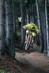 Mountain biker jumping with speed on forest path