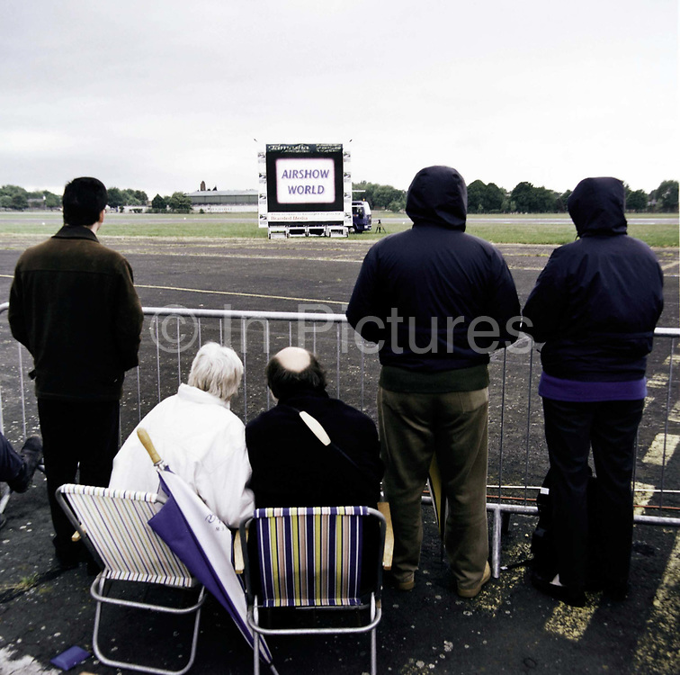 Waiting for an airshow display to commence, an aviation enthusiast family huddle in the cold at Mildenhall, a US Air Force base in Suffolk, England. Waiting for live TV coverage of the proceeding aerobatics to start, the people look miserable by their body language - hands thrust deep in pockets on this chilly afternoon and garden chairs providing welcome seats at the edge of the runway.