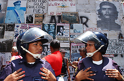 Two members of the Police watch a May Day march pass.  Police and National Guard where on hand to help control the opposition March which went through the heart of downtown, traditionally Chavista area.  Supporters and opposition to the president clashed at various points during the march, reportedly leaving at least one dead and various wonded.