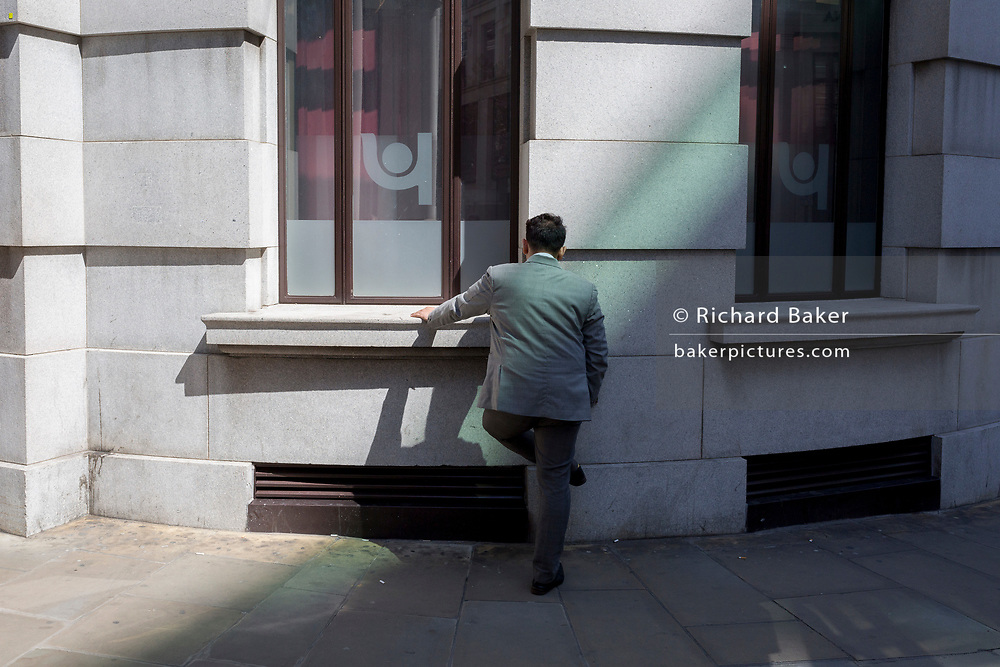 A businessman faces the wall of an office building wall in the City of London, the capital's ancient, financial district, on 14th May, in London, England.