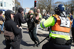 © Licensed to London News Pictures . 21/04/2013 . Brighton , UK . Police scuffle with antifascist protesters dressed in black . Nationalist group March for England hold a march along Brighton seafront today (Sunday 21st April) . The group was supported by supporters of the English Defence League and opposed by anti fascist and left wing groups . The annual march takes place close to St George's Day and frequently results in scuffles and violence between opposing groups and police . Photo credit : Joel Goodman/LNP