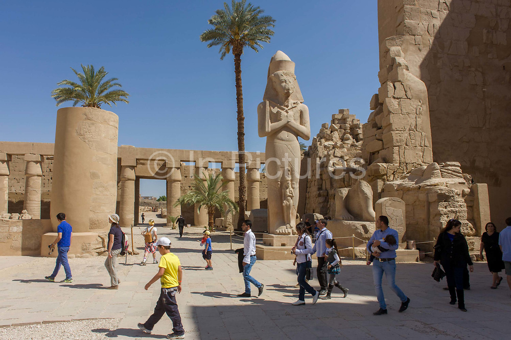 Tourists walk past the giant colossus of Pharaoh Ramesses ll and his daughter Bintanath at the ancient Egyptian Temple of Karnak, Luxor, Nile Valley, Egypt. Bintanath (or Bentanath) was the firstborn daughter and later Great Royal Wife of the Egyptian Pharaoh Ramesses II and is depicted on statues of her father at least three times in Karnak and Luxor though most famously here. According to the country's Ministry of Tourism, European visitors to Egypt is down by up to 80% in 2016 from the suspension of flights after the downing of the Russian airliner in Oct 2015. Euro-tourism accounts for 27% of the total flow and in total, tourism accounts for 11.3% of Egypt's GDP.