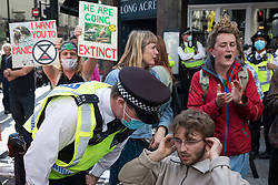 A Metropolitan Police officer asks an environmental activist from Extinction Rebellion to move out of a road in the Covent Garden area during the first day of Impossible Rebellion protests on 23rd August 2021 in London, United Kingdom. Extinction Rebellion are calling on the UK government to cease all new fossil fuel investment with immediate effect. (photo by Mark Kerrison/In Pictures via Getty Images)