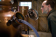 Keith Bodine filling a pot still at Sweetgrass Winery, Union, Maine.