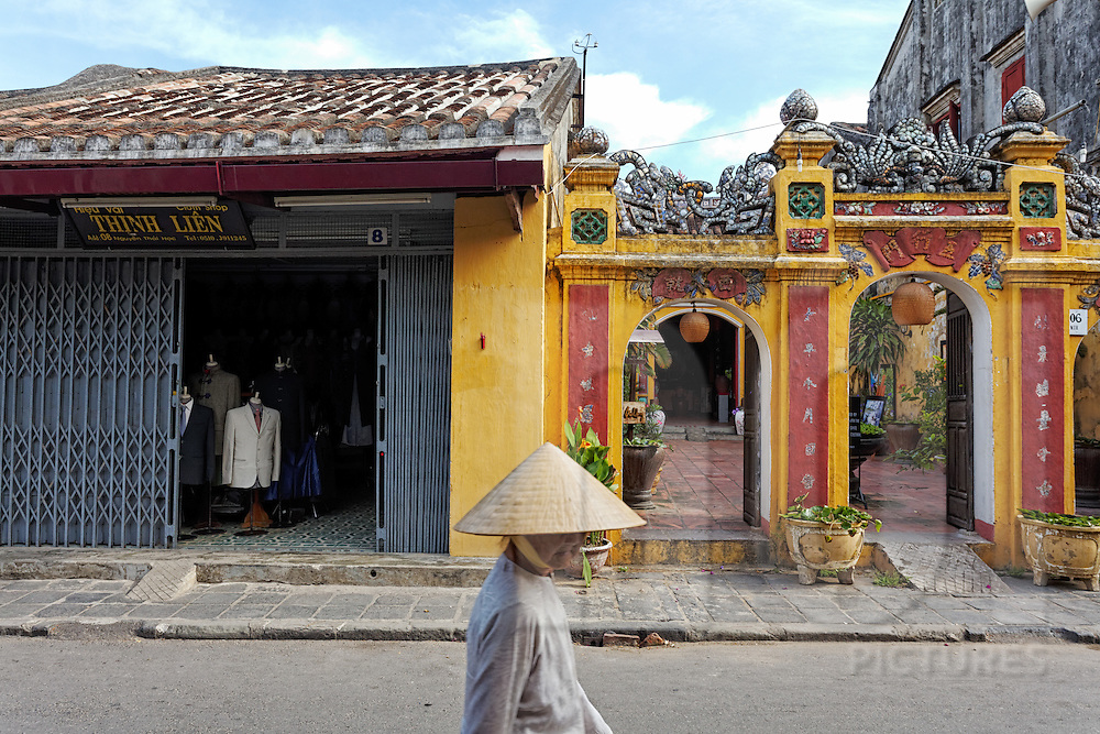 An elderly woman wearing a conical hat walks along a lane lined with pagodas and tailors shops in Hoi An, Vietnam, Southeast Asia
