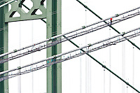 Third Tacoma Narrows Bridge construction ironworkers walk up the suspension cables, (the new bridge will carry eastbound traffic on Washington State Route 16 from the Kitsap Peninsula across the Tacoma Narrows, a part of Puget Sound, Tacoma, Washington, USA (July 2006) (The first bridge at this location was called Galloping Gertie and was destroyed in a windstorm in 1940 soon after its construction was complete.)