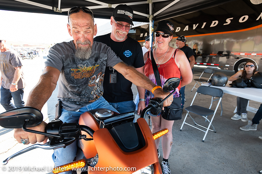 With the help of Steve Martin Staff, a staff tech in the Harley-Davidson PDC Dyno Lab, Duke Barber and Amy Ryan from Fulton NY took a break from their pre-wedding Sturgis honeymoon to check out the Livewire electric motorcycle Jumpstart display at the Harley-Davidson Garage at the Full Throttle Saloon during the  during the Sturgis Black Hills Motorcycle Rally. Sturgis, SD, USA. Tuesday, August 6, 2019. Photography ©2019 Michael Lichter.