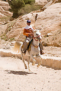 Middle East, Jordan, Petra, UNESCO World Heritage Site. Local Bedouin riding a horse. April 2008