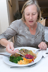 Customer in Polish restaurant eating Golabki dish with pickled beetroot,