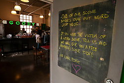 """A sign outside a coffee shop at Fort Mason advises regular customers that they could be in line for a free scone if they had purchased a """"weird"""" one the previous week, photographed Sunday, April 15, 2018, in San Francisco. (Photo by D. Ross Cameron)"""