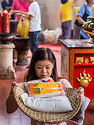 """26 AUGUST 2013 - BANGKOK, THAILAND:     A woman prays before donating rice and staples to the Poh Teck Tung Foundation for Hungry Ghost Month in Bangkok. Poh Teck Tung operates hospitals and schools and provides assistance to the poor in Thailand. The seventh lunar month (August - September in 2013) is when the Chinese community believes that hell's gate will open to allow spirits to roam freely in the human world for a month. Many households and temples will hold prayer ceremonies throughout the month-long Hungry Ghost Festival (Phor Thor) to appease the spirits. During the festival, believers will also worship the Tai Su Yeah (King of Hades) in the form of paper effigies which will be """"sent back"""" to hell after the effigies are burnt.   PHOTO BY JACK KURTZ"""
