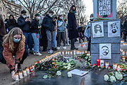 A participant lays a candle at a memorial during a demonstration, commemorating the anniversary to the Hanau terror attack, in Berlin, Germany, February 19, 2021. About 800 participants took part in the event in remembrance of the Hanau shootings, in which ten people were killed and five others wounded. The shooting spree was committed on February 19, 2020 by a far-right extremist targeting two shisha bars and kiosks at the Hessian city of Hanau near Frankfurt. The gunman was identified as 43-year-old Tobias Rathjen. The majority of the victims were Germans with migrant backgrounds, among the victims was also the perpetrator's mother. (Photo by Omer Messinger)