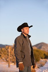 handsome cowboy at sunset looking at the mountains