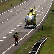 NLD/Blaricum/20050711 - Gekantelde vrachtwagen met gewonde chauffeur snelweg A27 ter hoogte Blaricum, helicopter, heli, lifeliner, arts