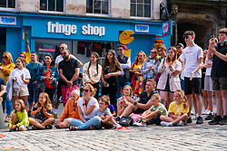 Edinburgh, Scotland, UK. 4th August  2021.  Edinburgh City Centre and Old Town busy this afternoon in warm sunny weather. Pic; Audience watch street performer during show on the Royal Mile.  Iain Masterton/Alamy Live news.