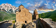 Pictures & images of Gergeti Holy Trinity (Tsminda Sameba) Georgian Orthodox and Apostolic Church and bell tower, 14th century, Gergeti, Khevi province, Georgia (country). At Sunset. .<br /> <br /> Visit our MEDIEVAL PHOTO COLLECTIONS for more   photos  to download or buy as prints https://funkystock.photoshelter.com/gallery-collection/Medieval-Middle-Ages-Historic-Places-Arcaeological-Sites-Pictures-Images-of/C0000B5ZA54_WD0s<br /> <br /> Visit our REPUBLIC of GEORGIA HISTORIC PLACES PHOTO COLLECTIONS for more photos to browse, download or buy as wall art prints https://funkystock.photoshelter.com/gallery-collection/Pictures-Images-of-Georgia-Country-Historic-Landmark-Places-Museum-Antiquities/C0000c1oD9eVkh9c