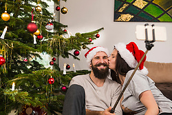 Couple taking selfie while kissing at home