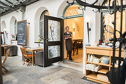 Interior of cafÈ with owner holding tablet and leaning by door