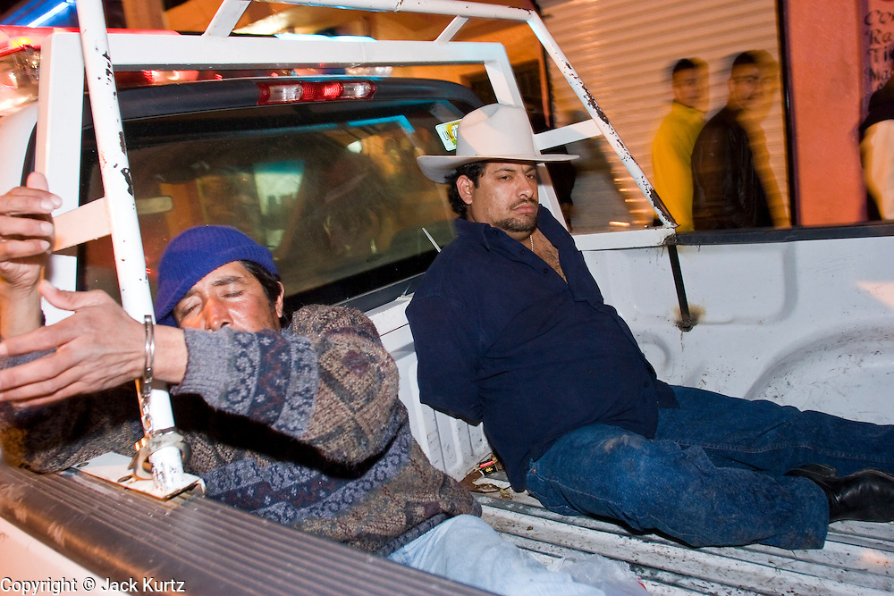"""05 FEBRUARY 2005 - NOGALES, SONORA, MEXICO: Men who were arrested by Nogales police sit in the back of a police truck during an anti-gang sweep. Members of """"Grupo Operativos"""" a special operations unit of the Nogales, Sonora, Mexico, police department, on patrol in Nogales, Saturday night, Feb. 5. The Operativos specialize in anti-gang enforcement and drug interdiction missions. In recent months they have stepped up patrol activity in Nogales communities near the border. In January 2005, the US Department of State has issued a travel advisory advising US citizens to avoid travel along the US Mexican border because of increased violence, including the kidnapping of US citizens, in border communities. Most of the violence has been linked to the drug cartels, who are increasingly powerful in Mexico. The Operativos also patrol the districts of Nogales frequented by US tourists in an effort to prevent crime directed against US citizens.   PHOTO BY JACK KURTZ"""