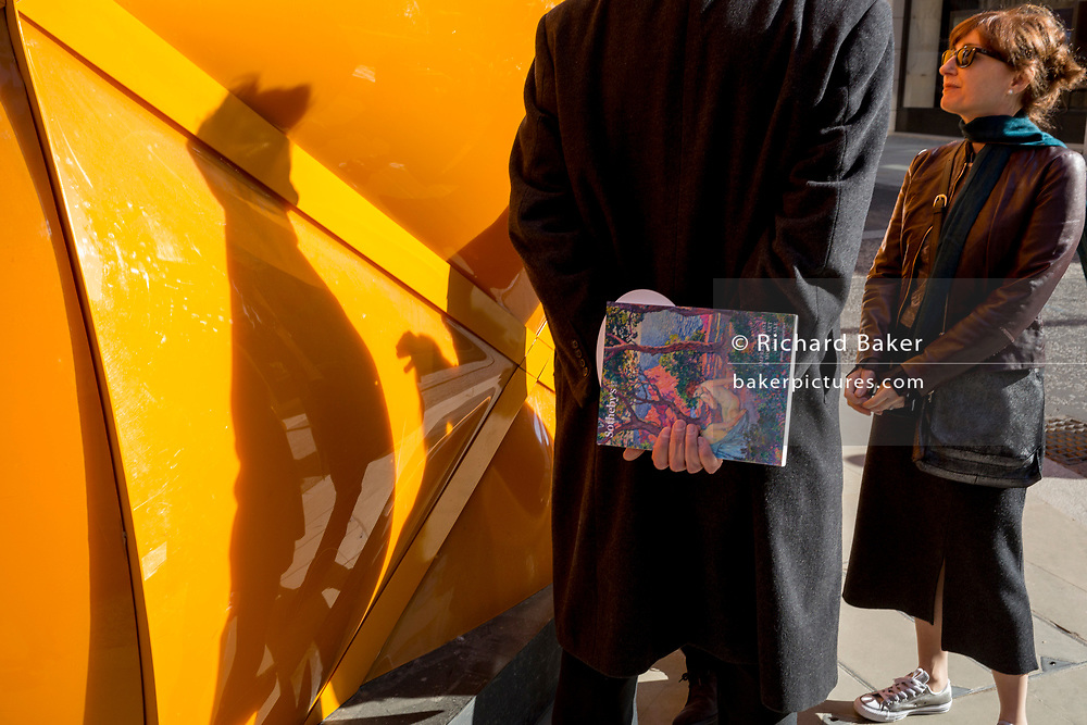 Associates hold a conversation after spontaneously bumping into each other beneath the temporary renovation hoarding of luxury brand Louis Vuitton in New Bond Street, on 27th February 2019, in London, England.